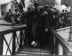 Harold Bride, surviving wireless operator of the TITANIC, with feet bandaged, being carried up ramp of ship