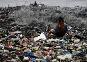 A boy is hit by waves as he collects recyclable materials from garbage washed onto the shore along Manila Bay in Manila on August 27, 2011. (Cheryl Ravelo/Reuters)