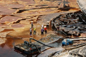 Workers drain a leaking sewage tank at a copper mine in Shanghang, China on July 13, 2010. One of China's biggest gold producers was ordered to pay $4.62 million by a local court for a toxic spill. The court also issued prison terms ranging between three years to 42 months to five staff who were found to be involved in the incident, which affected water supplies for 60,000 people. (Stringer/Reuters)