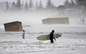 A surfer walks past cargo containers washed ashore from the stricken container ship Rena at Waihi Beach, New Zealand on January 10, 2012. Half of the ship Rena, stranded on a New Zealand reef for more than three months, sank after breaking up in rough seas and littering beaches with cargo and debris. (Brendon O'Hagan/Bloomberg)