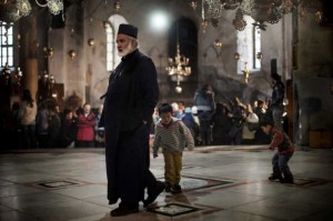 Children play on the heels of a Christian Orthodox priest inside the Church of the Nativity in Bethlehem, West Bank. Photo Credit: Marco Longari / AFP.